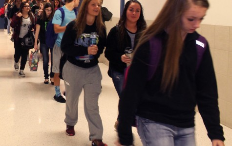 Students are walking in the hall during passing period.