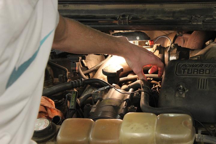 Sophomore Jesse Falkena adjusts the engine on the new, donated Volkswagen diesel engine.
