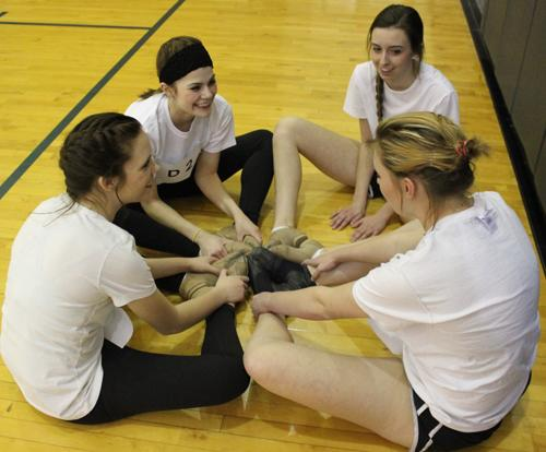 Juniors Sydney Patterson, Erica Whipple, Tierney McPike, and sophomore Tearyn Wilson stretch in a circle to prepare for Pacer tryouts
