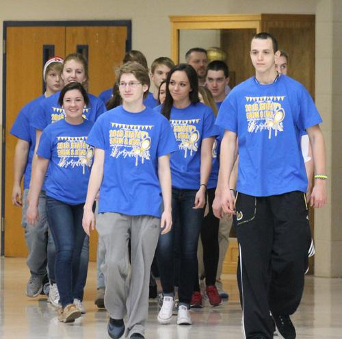 The state qualifying swimmers and divers walk through the tunnel of students on the way to state