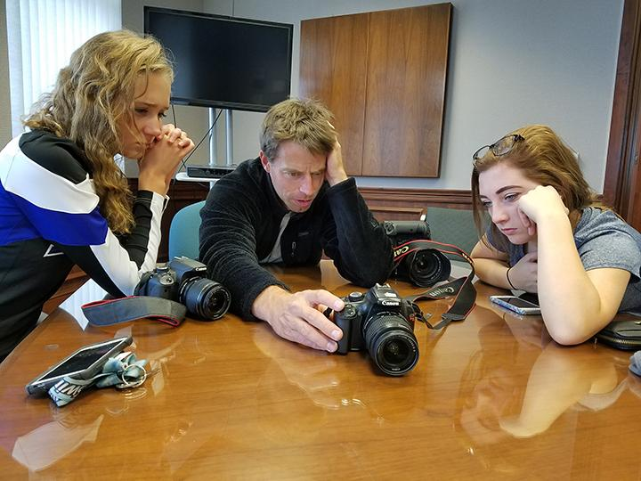 National Geographic photographer Brian Lehmann analyzes photos with senior Syble Heffernan and junior Phoenix VanCura while shooting around various locations in North Platte.