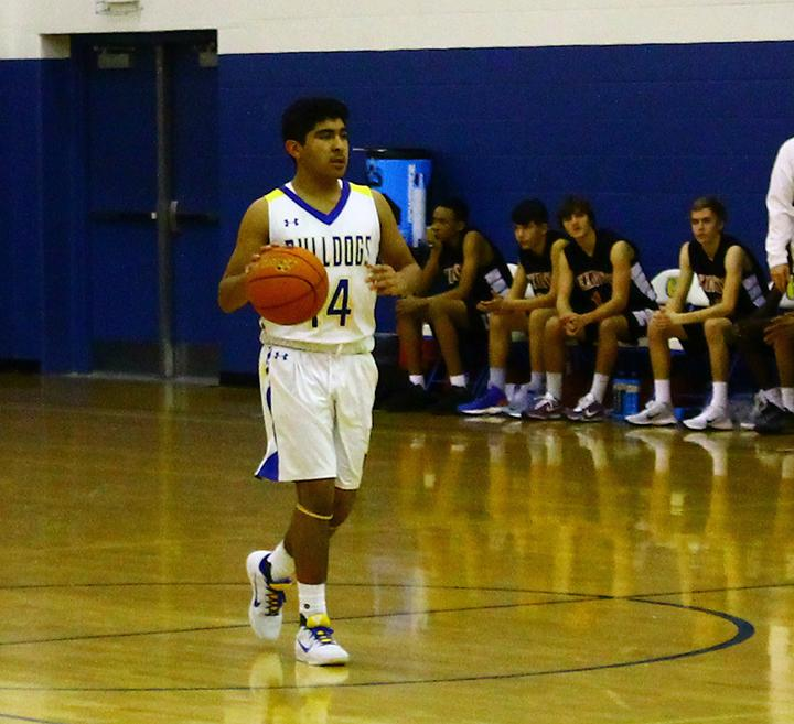 Freshman Derrick Ramos surveys the court while walking the ball up the hardwood in North Platte's 45-25 home win against Lexington on Dec. 13, 2016.