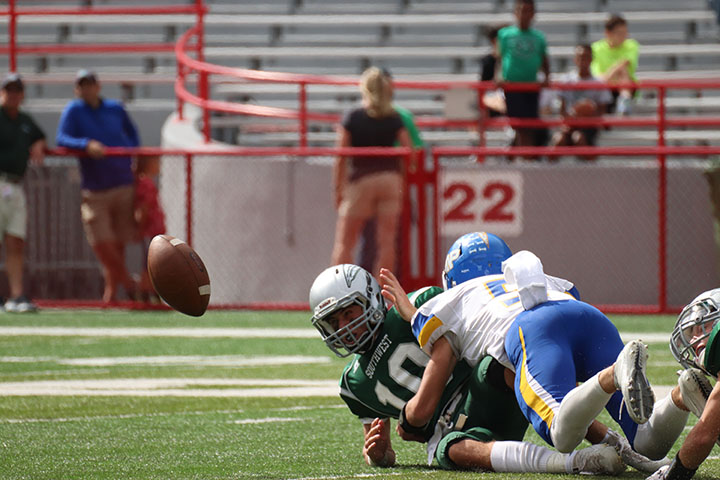 Senior Caden Comer tackles a Lincoln Southwest player, making him lose the ball.