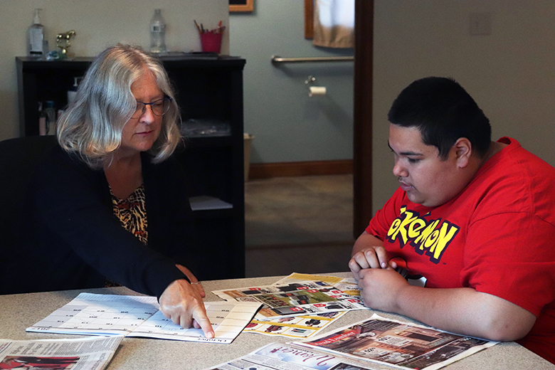 Jared Snyder goes over the calendar for the week with paraprofessional Cindy Stark. He said his favorite place to work through the Transition House program is at Wild Bills.