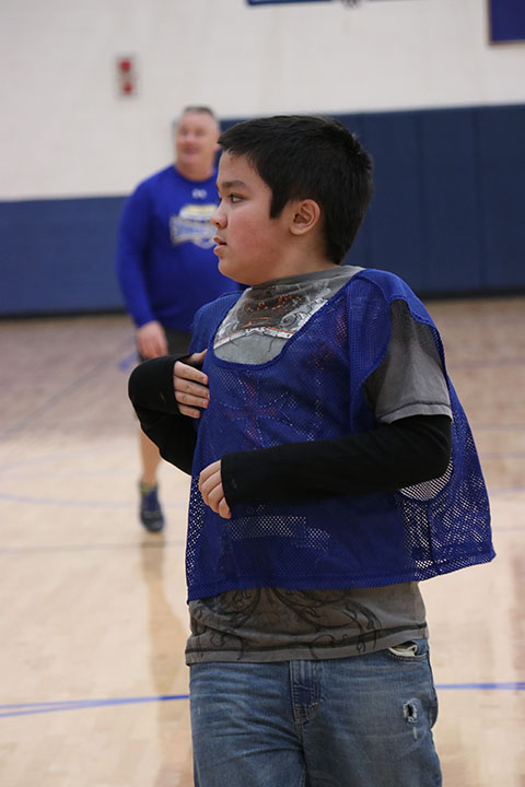 Student plays basketball with his peers in the inclusive P.E. class, while teacher Brian Jahnke watches.