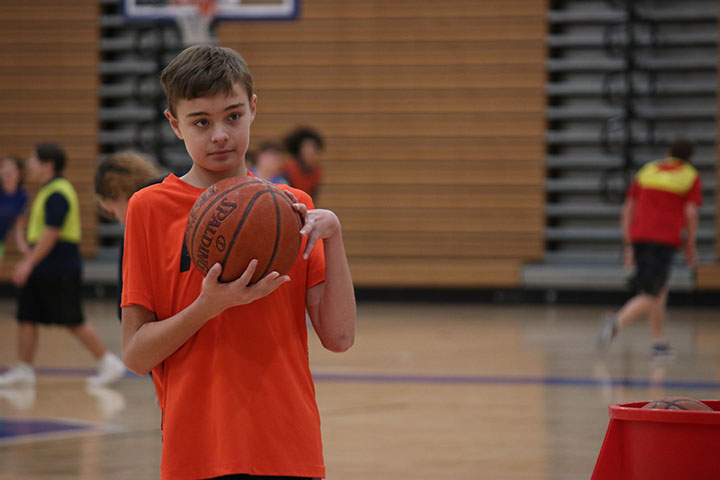 Student grabs a new basketball and prepares to shoot a basket.