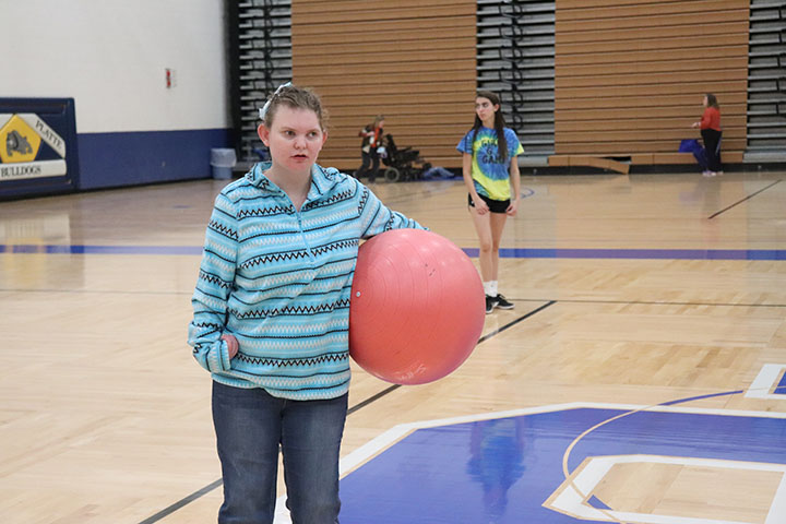 Student holds the exercise ball as the class prepares to play adaptive volleyball.