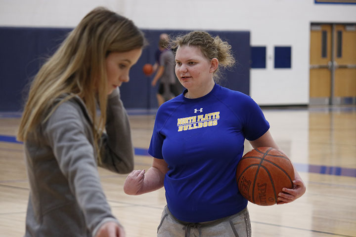Student aid helps another student practice her basketball skills.