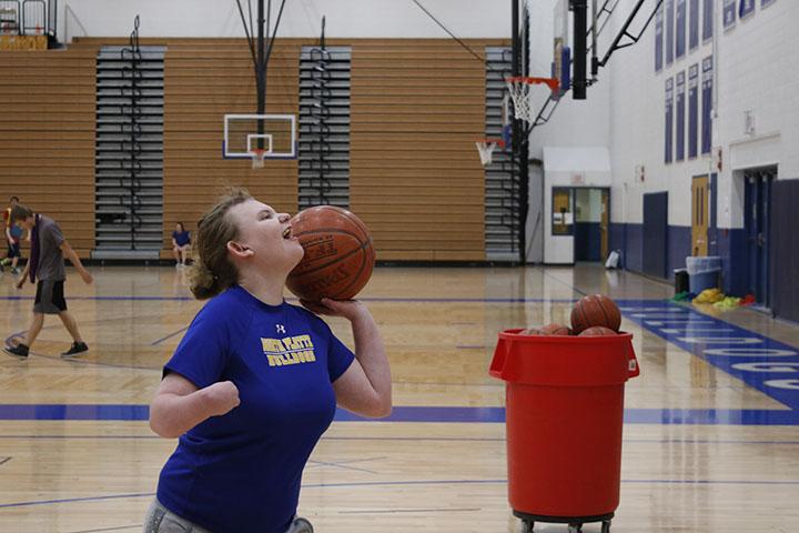 Student shoots basket.