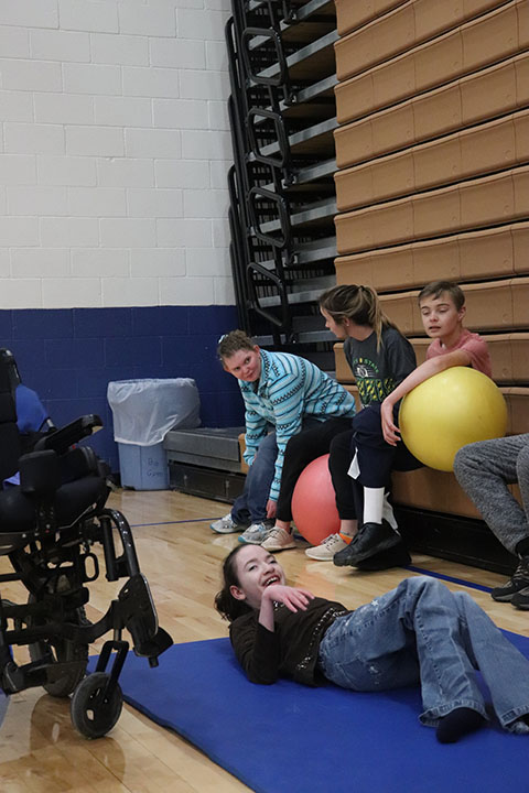 The students with multiple and severe disabilities sit as they get ready to start regular education gym class.
