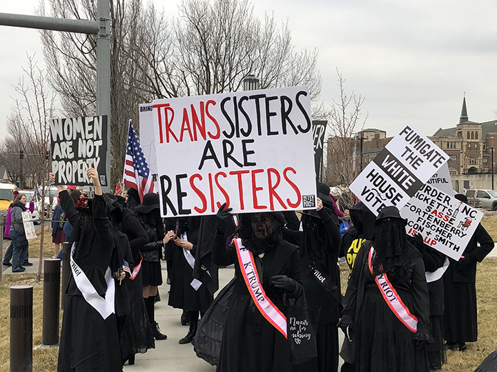 Anonymous women hold dighns and wear sashes protesting the Trump administration and supporting other women at the Women's Anniversary March on Lincoln.