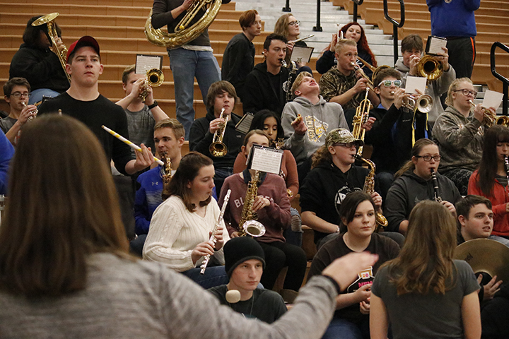 Junior Monique Carlock leads the pep band while they play Sweet Caroline during the game.