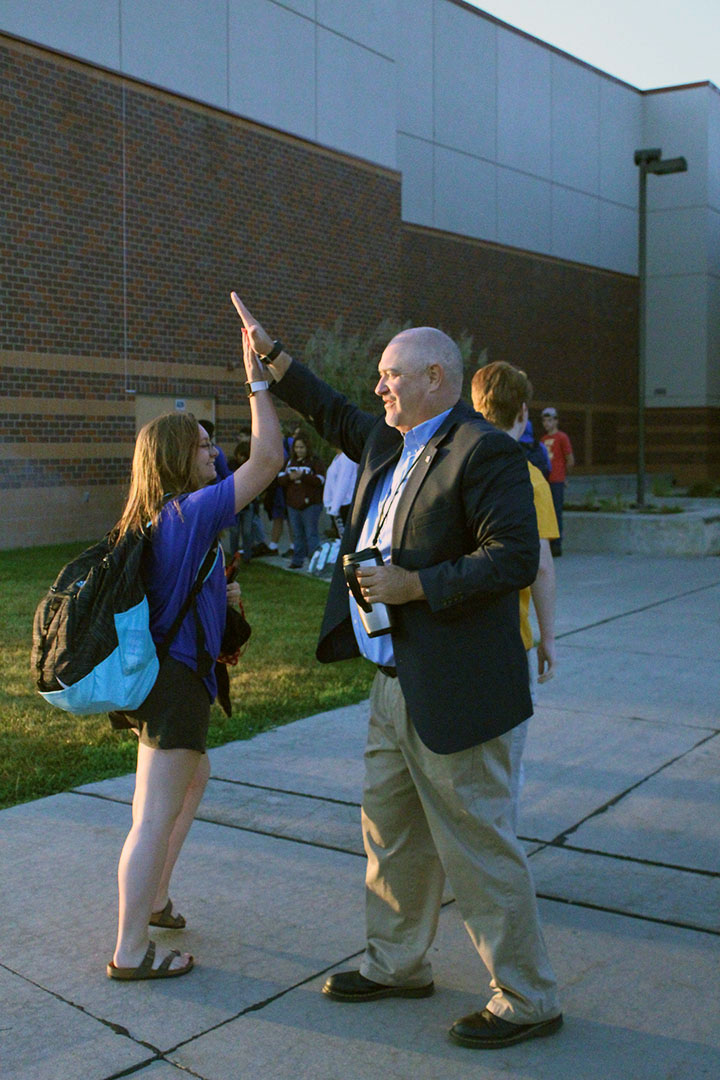 "Assistant principal John Byrn gives a high-five to senior Haley Ablard on High-Five Friday. ""I try to get all of [the students], but a couple of them sneak by, and that's okay."" Byrn said."