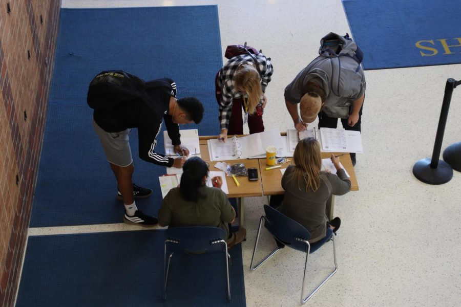 """Students fill out the sign out sheet at the front of North Platte High School. Senior Daphanie Ham thinks the sign out system is inconvenient. """"It's ridiculosly unorganized,"""" she said. However, the administration remains optimistic. """"It takes a little bit of time to get these things in place,"""" superintendent Ron Hanson said."""