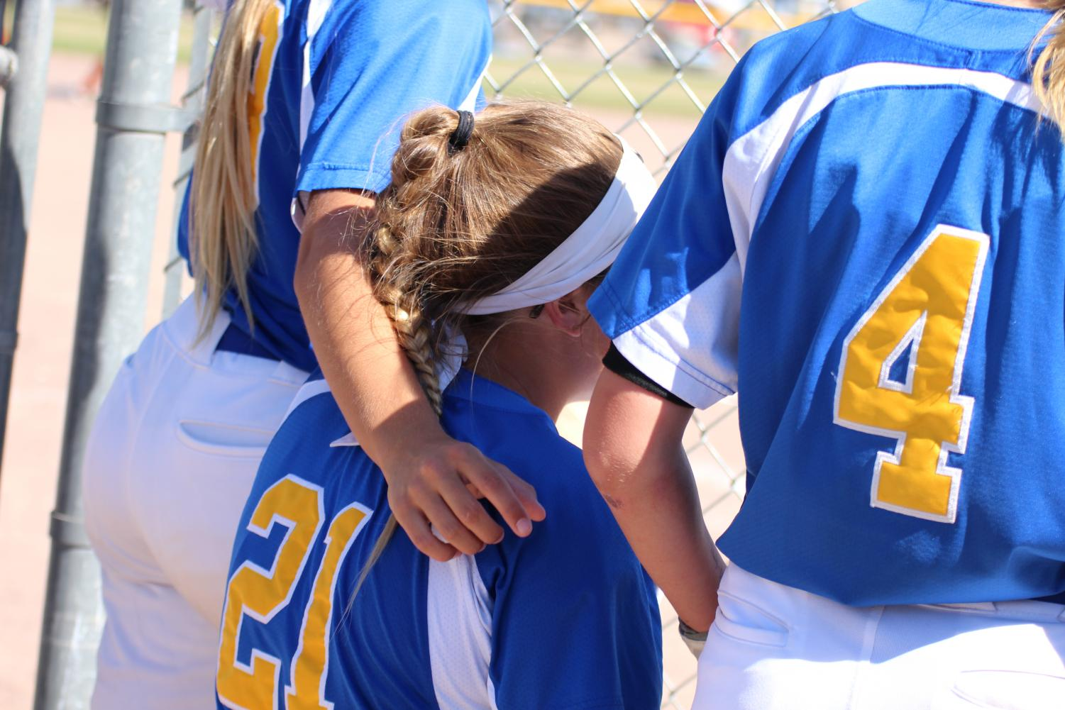 Junior Taylor Chitty puts her arm around teammate Josie Freeze during their home tournament on September 15, 2018. The team ended up taking first on their own dirt. Photo by Sophia Chingren.