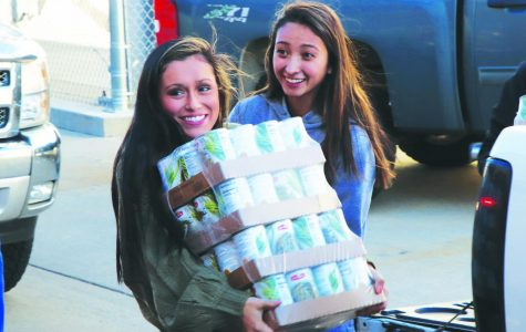 """Seniors Alecea Comer (left) and Aniston Manzano unload cans during the """"senior parade"""" at the NPHS canned food drive on Nov. 16."""