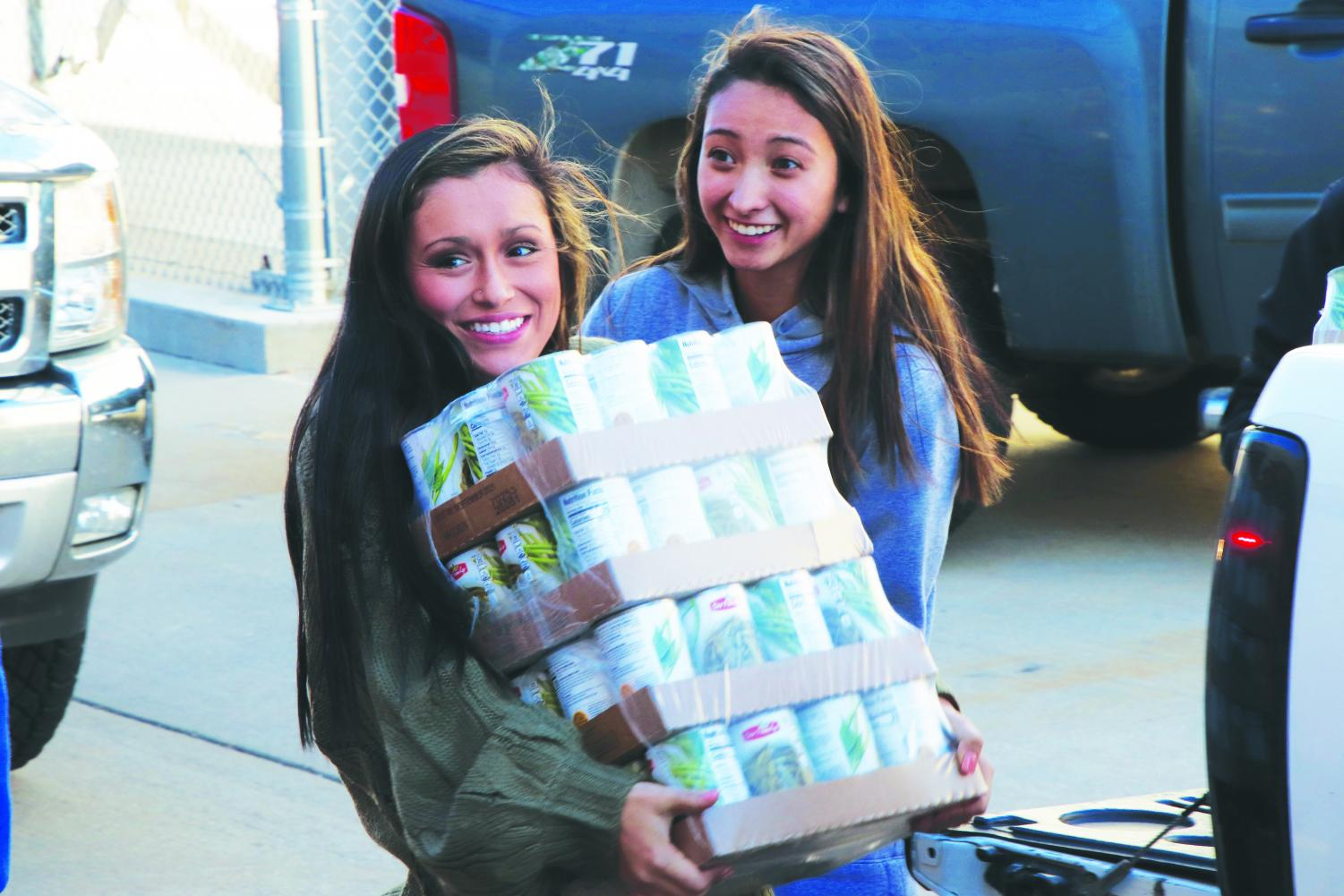 "Seniors Alecea Comer (left) and Aniston Manzano unload cans during the ""senior parade"" at the NPHS canned food drive on Nov. 16."