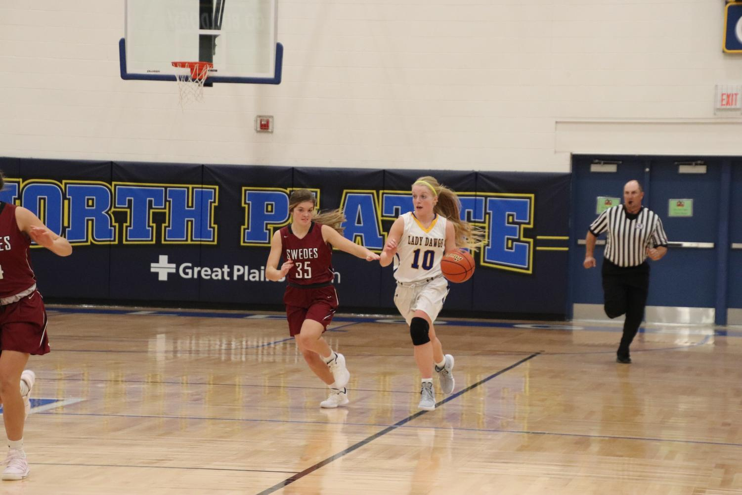 "Senior Abbie Hedgecock drives down the court in the girl's first scrimmage versus Gothenburg. ""We have a really good chemistry. We can play with each other, criticize each other, but also really help each other out,"" she said."