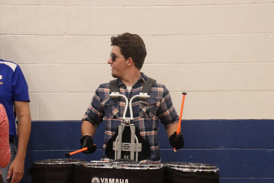 Senior Luke Armstrong holds a steady conversation with band teacher Brett Bradley while playing the drums.