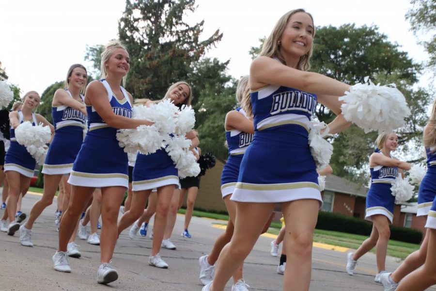 Cheerleaders+perform+a+routine+while+marching+during+the+Homecoming+parade.