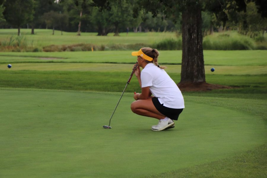 Karsen Morrison looks at the landscape of the green to plan her put.