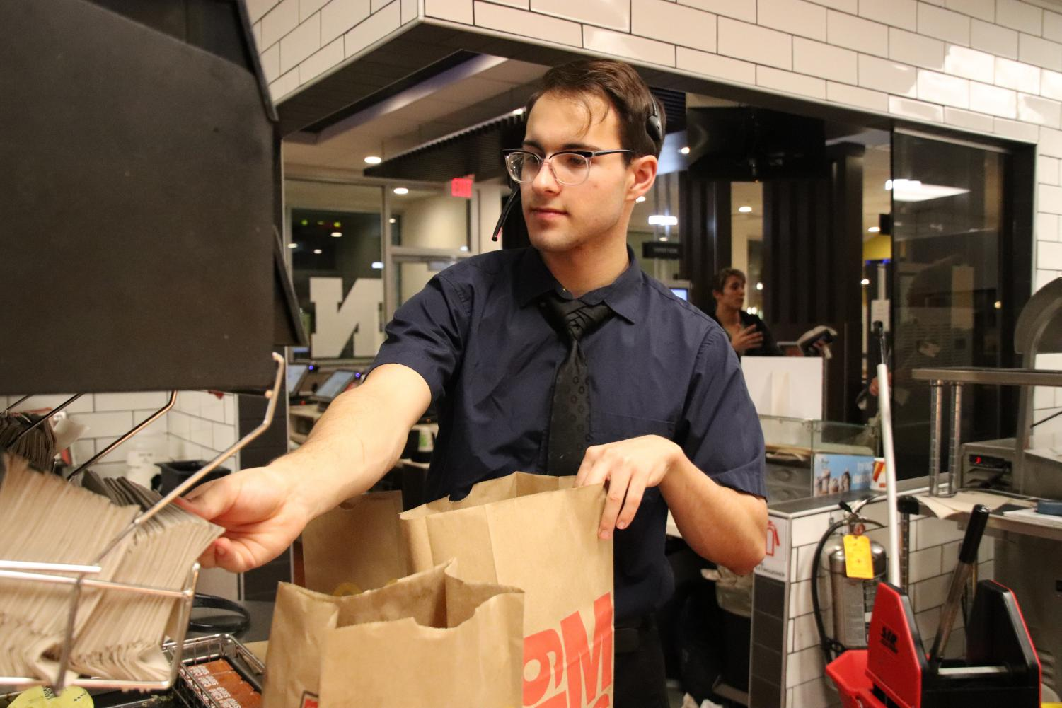 "Junior Will Kramer working the night shift at McDonald's. ""I like the challenge of running around and covering three positions, but inside you're mentally screaming,"" he said."