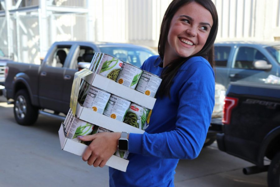 Senior Savanna States carries cans into the dawg pound at the canned food drive on Nov. 15. The seniors had a point total of 46,819.