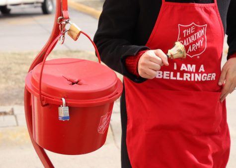 "Bell ringers stand next to the red kettle to collect money. ""The money raised supports our operation or ministries all throughout the year,"" Poff said."