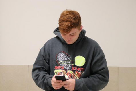 "Senior Carter Lukas poses for a picture. Lukas often is on his phone before school. ""I just chill for like thirty minutes,"" said Lukas."