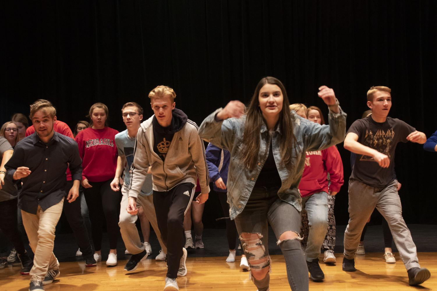 Actor Joel Bradley is practicing choreography behind Ciera Carlson. Carlson is helping the cast keep on time to the music by snapping.