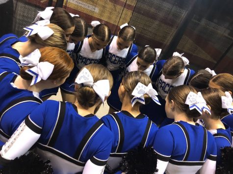 "The Pacer dance team huddles to pray at state dance. ""Its a good luck thing,"" said sophomore Olivia Eckel. The pacers competed in jazz and pom."