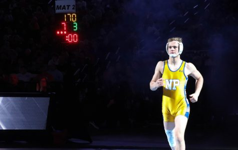 "Junior Gavyn Brauer enters the arena on Feb. 22 at the CHI Health Center in Omaha for the championship match against Columbus' Anthony DeAnda in the 182 weight class.  ""It was nerve-wracking. Walking through the tunnel and the spotlights, I got nervous,"" Brauer said."