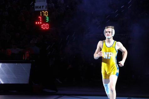 Junior Gavyn Brauer enters the arena on Feb. 22 at the CHI Health Center in Omaha for the championship match against Columbus