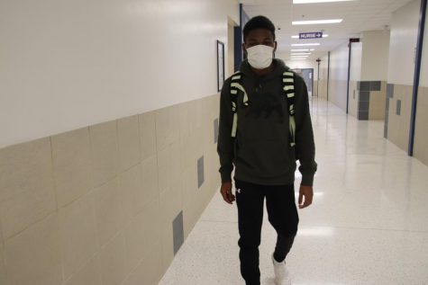 Junior Shemar Palmer demonstrates wearing a sick mask in school. Complete Family Health offers and recommends masks to people who have a bad cough.