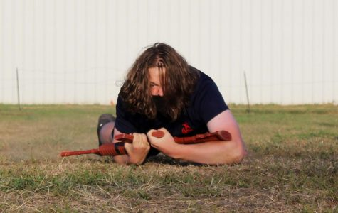 Senior Alex Cook painfully crawls across a field by the mall.