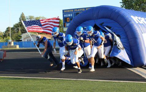 The Bulldog's Varsity Football team runs onto the field to kick off the game.