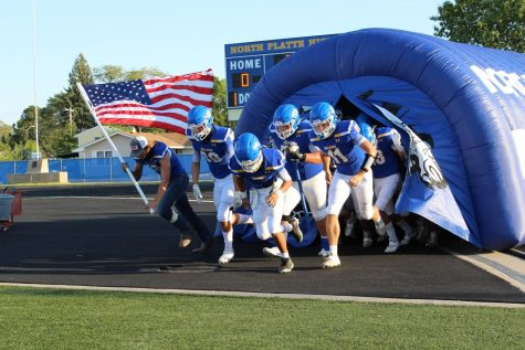 The Bulldog's Varsity Football team runs onto the field to kick off the game.