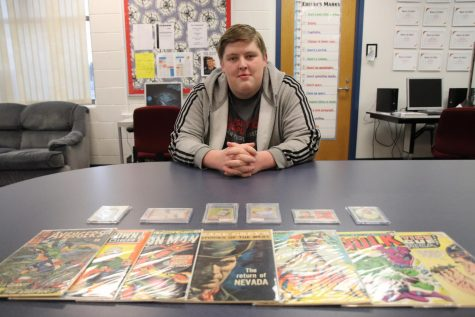 Senior Jacob Godfrey poses in front of some of his collected items. These items include vintage comics and sports trading cards.