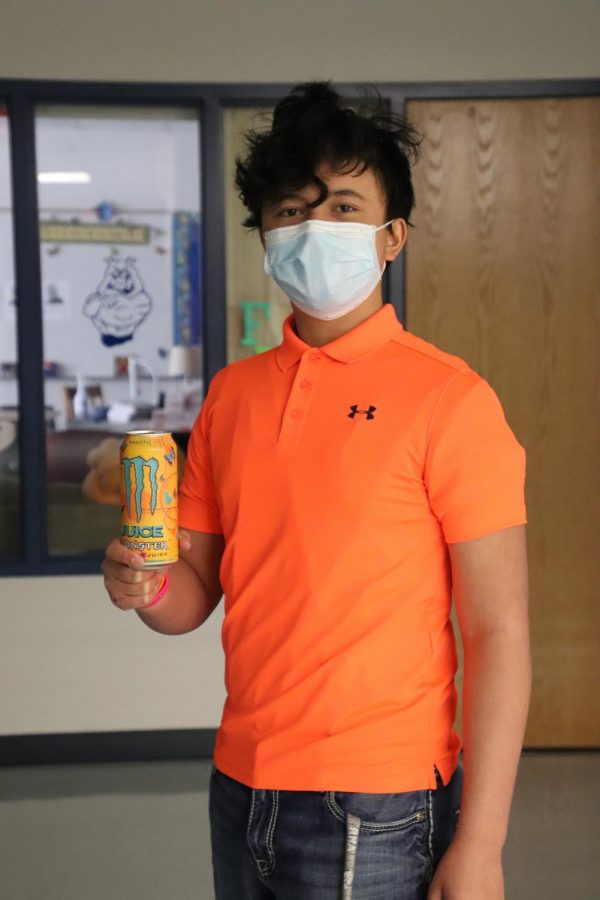 Sophomore Tony Booth poses in his orange outfit to match his energy drink.