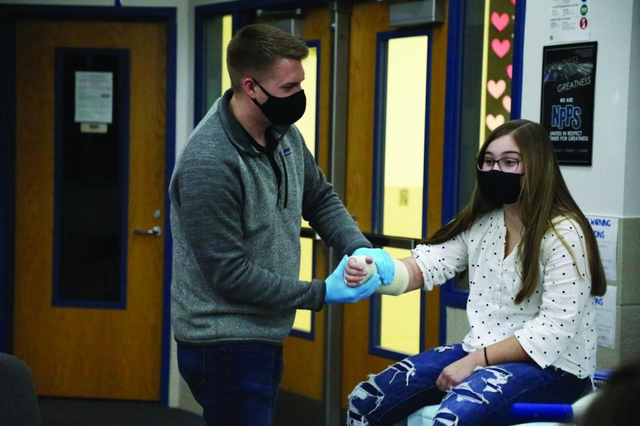 Medical club president Ellie Fisher helps demonstrates a wrist cast.