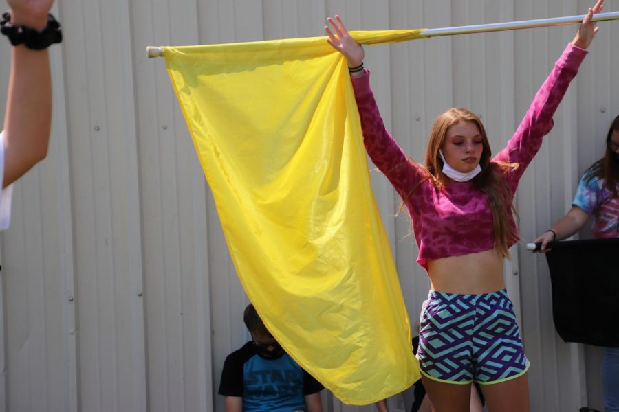 Freshman Justina -last name- practicing with the flags during color guard's practice.
