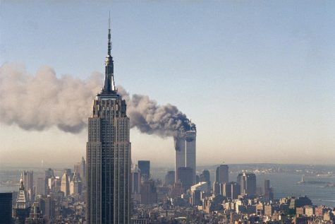 The twin towers of the World Trade Center burn behind the Empire State Building in New York, Sept. 11, 2001. In a horrific sequence of destruction, terrorists crashed two planes into the World Trade Center causing the twin 110-story towers to collapse.